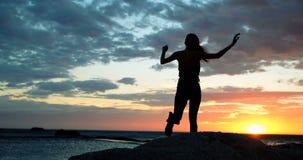Women standing on rock at beach during dusk 4k. Silhouette of women standing on rock at beach during dusk 4k stock footage