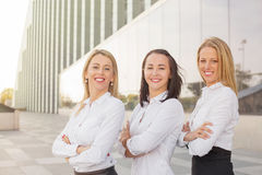 Women standing and smiling with their hands crossed Royalty Free Stock Photography