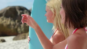 Women standing by the surfboard pointing outwards. While at the beach stock footage