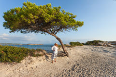 Women standing under the pine wood on sandy beach Royalty Free Stock Images