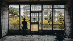 Women standing at window in abandoned holiday resort. Moody royalty free stock photos
