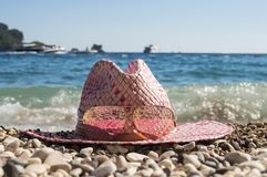 Women`s straw beach hat sunhat with sunglasses lies on the pebble beach, surrounded by round stones on a background of blue sea
