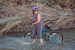 Women in stream with bike. Women in stream with mountain bike stock photos