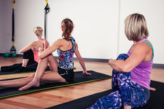 Women stretching their backs in gym. A small group of women are stretching their backs in the gym royalty free stock images