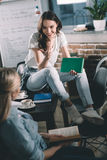 Women students having conversation while studying together Royalty Free Stock Photos