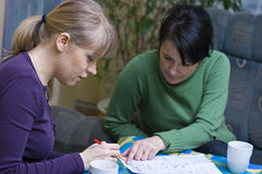Women studying house plan. Close up of two women studying architectural plan of house Stock Photography