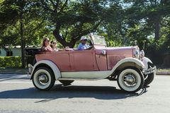 Antique Ford Roadster, young women having fun in pink Ford Roadster, Havana, Cuba stock photos