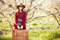 Women with suitcase in blossom apple tree garden Stock Photos