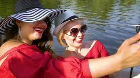 Women in summer outfits taking selfie photo on sailing boat. Smiling young women in summer outfits relaxing on sailing boat. Female friends taking selfie photo stock video