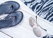 Women summer slippers, scarf and sunglasses in a zebra print. On a white wooden background stock photography