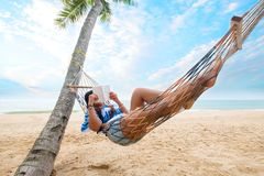 Women sunbathe relax and reading a book on hammock Stock Images