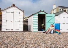 Women sunbathing outside beach hut at Seaton. Devon, UK. Part of the Jurassic coast Royalty Free Stock Photos