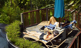 Women sunbathing beside pool Royalty Free Stock Image