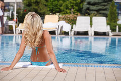 Women sunbathing. Rear view of blond hair women sunbathing on th Stock Photo