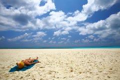 Woman is sunburning on the beach Stock Photos