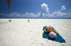 Women is sunburning on the sandy beach. Young women is sunburning on the coral sandy beach, Maldives stock photo
