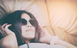 Women with sunglasses lying on a sofa listening to music royalty free stock images