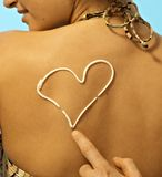 Women with sunscreen heart sign on back Stock Image