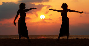 Women at sunset. Dramatic image of two women by the ocean at sunset Stock Photo