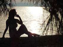 Women in the sunset. Beautiful woman sitting on the beach and enjoy the sea and the sunset, photography Stock Images