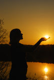 Women and sunset. Silhouette woman with  sun in  hands Stock Image
