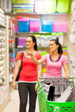 Women in supermarket. Two young women walking in supermarket with trolley Royalty Free Stock Photos