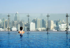 Women in a swimming pool. On the roof admiring a cityscape Stock Photo