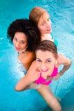 Women swimming in pool. Friends wearing bikinis bathing in swimming pool Stock Photos