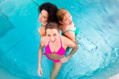 Women swimming in pool. Friends wearing bikinis bathing in swimming pool Stock Photo