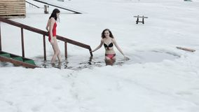 Women bathing in the ice hole. Women in swimsuits descend into an ice hole and are dipped stock video