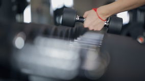 Women take dumbbells for sports, close up. The image is blurring and jitter from time to time. Two lovely females exercise in gym at rack with sport stock stock video footage