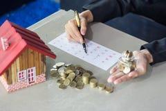 Women take notes on monthly savings, Savings money jar full of c royalty free stock images