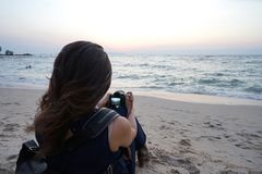 Women take a picture of the sea. Women take a picture of the senset and sea royalty free stock images
