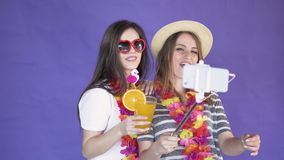 Women take a selfie. Delighted young women taking selfie with a selfie stick, wearing hawaiian wreaths around the slim necks, isolated shot in the purple stock video footage