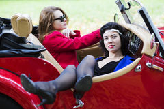Women take vocation ride on red car Royalty Free Stock Image