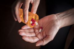 Women take white and red capsule with right hand from a ambar Stock Images