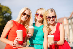 Women with takeaway coffee cups in the city. Holidays and tourism, friends, blonde girls concept - beautiful women with takeaway coffee cups in the city Royalty Free Stock Images