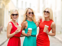 Women with takeaway coffee cups in the city. Holidays and tourism, friends, blonde girls concept - beautiful women with takeaway coffee cups in the city Royalty Free Stock Image