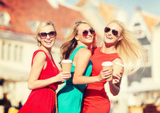 Women with takeaway coffee cups in the city. Holidays and tourism, friends, blonde girls concept - beautiful women with takeaway coffee cups in the city Royalty Free Stock Photography