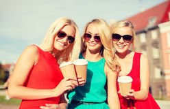 Women with takeaway coffee cups in the city. Holidays and tourism, friends, blonde girls concept - beautiful women with takeaway coffee cups in the city Stock Photography
