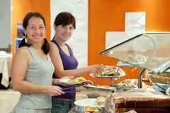 Women takes  pastry  in buffet Stock Images