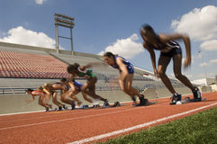 Women Taking Off From Starting Blocks Stock Photo