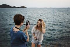 Women taking photo by seashore royalty free stock photo