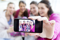 Women Taking A Selfie. Four women are sat at home in their pajamas talking a selfie. They are drinking champange and smiling Stock Photo