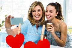 Women taking a selfie on mobile phone against red hanging hearts Stock Images