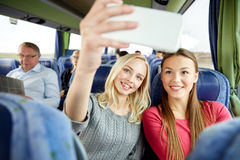 Women taking selfie by smartphone in travel bus Royalty Free Stock Photo