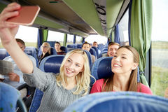 Women taking selfie by smartphone in travel bus. Transport, tourism, road trip and people concept - happy young women or friends in travel bus taking selfie by Royalty Free Stock Photo