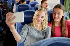 Women taking selfie by smartphone in travel bus Royalty Free Stock Images