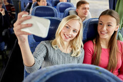 Women taking selfie by smartphone in travel bus. Transport, tourism, road trip and people concept - happy young women or friends in travel bus taking selfie by Royalty Free Stock Images