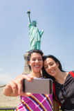 Women Taking a Selfie with Statue of Liberty stock photo